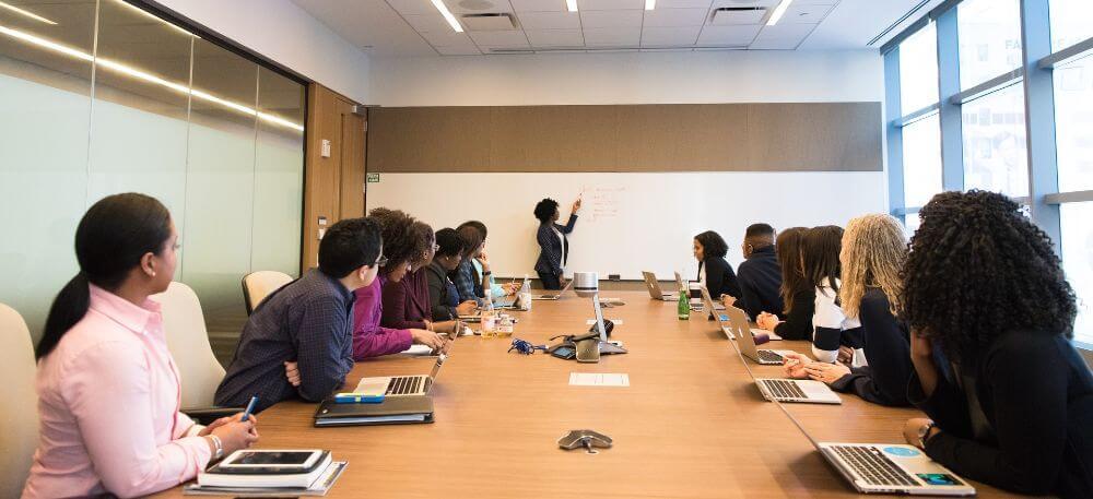En mellanstor grupp människor sitter runt ett bord i ett mötesrum och tittar på när någon presenterar något längst fram