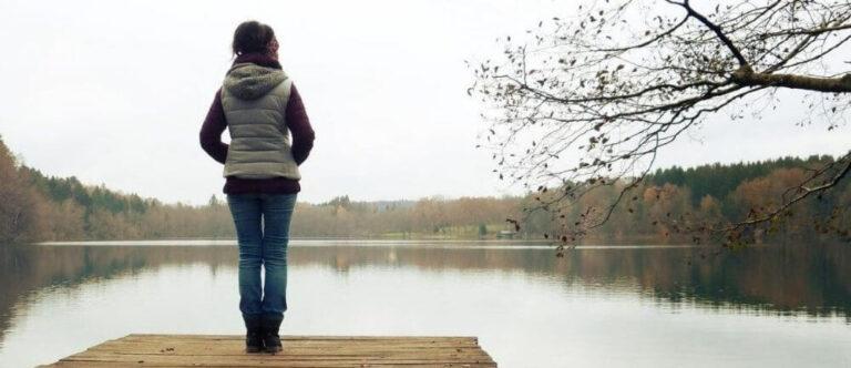 Missbruk, trauma, samsjuklighet. En kvinna står på en brygga och blickar ut över en sjö. Vädret är grått och dystert.