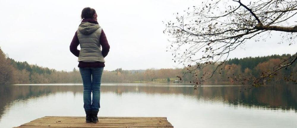 Missbruk, trauma och samsjuklighet. En kvinna står på en brygga och blickar ut över en sjö. Vädret är grått och dystert.
